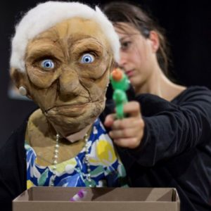 une marionnette de vieille dame brandit un pistolet à eau