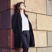Magali Mineur adossée à un mur regarde le ciel