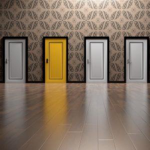 une porte jaune parmi les portes blanches