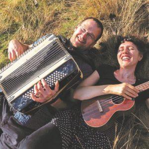 Régine Galle et Fabian Beghin dans l'herbe avec leur accordéon et leur ukulélé