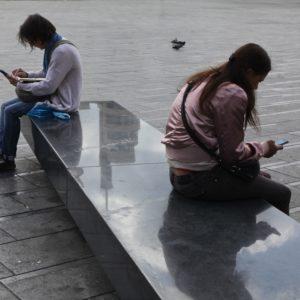 deux personnes assises sur un banc regardent chacune leur GSM