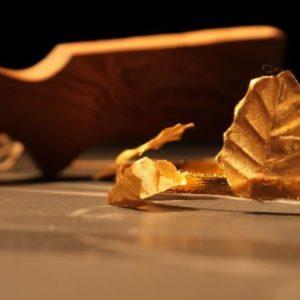 Un fusil et une feuille d'or déposés au sol
