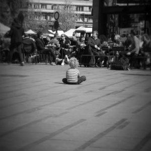 enfant assis de dos en tailleur sur une place, qui regarde des adultes assis en terrasse d'un café