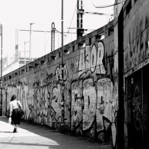 jeune femme qui marche le long d'un mur tagué